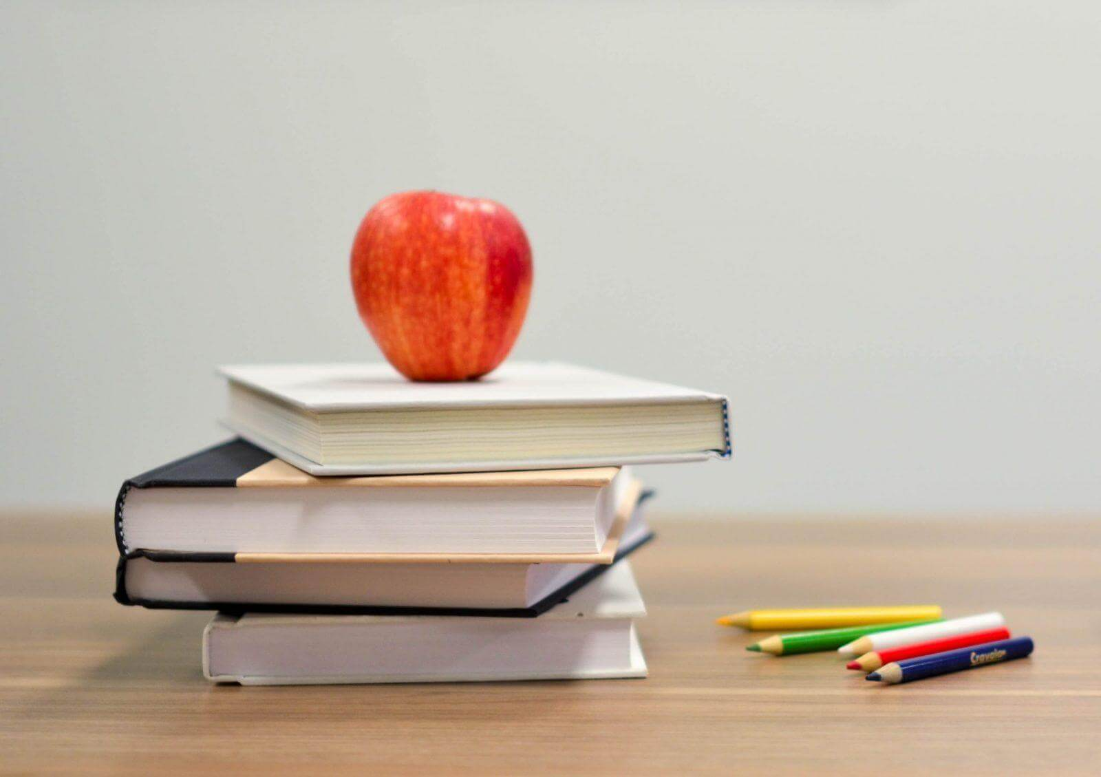 Red apple sitting on four books on wooden table